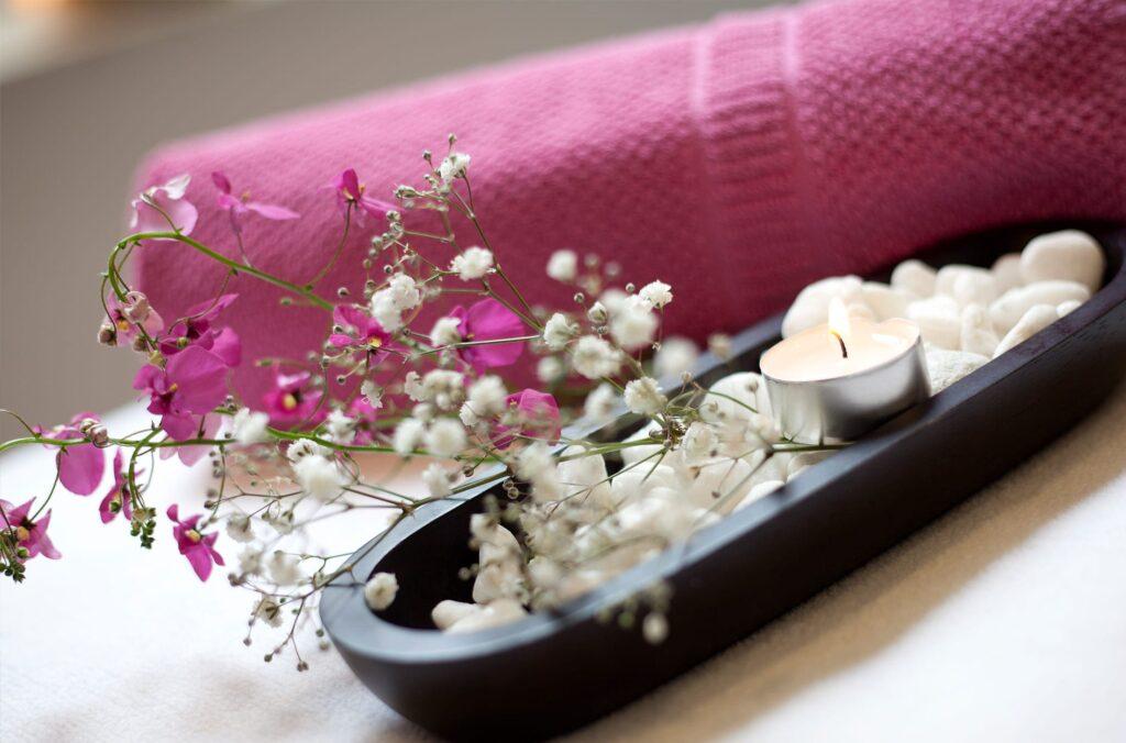 Wellness-Dekoration mit Blumen, Kerzen und Handtüchern